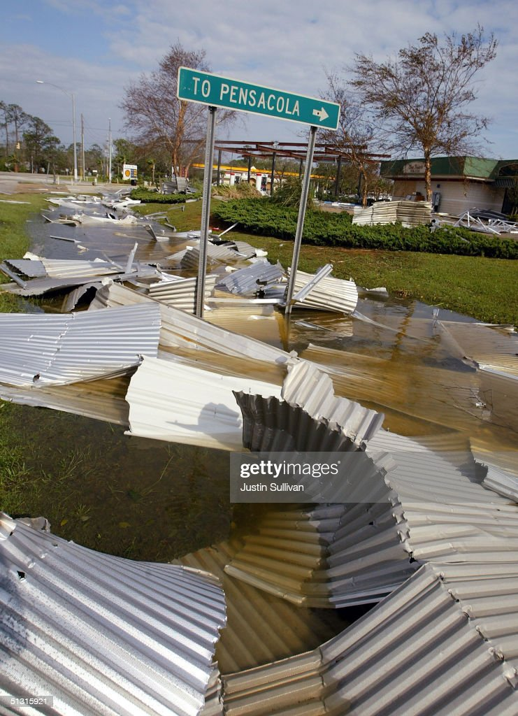 A Metal Roof Lies Next To A Sign Pointing To Pensacola, Florida September  16,