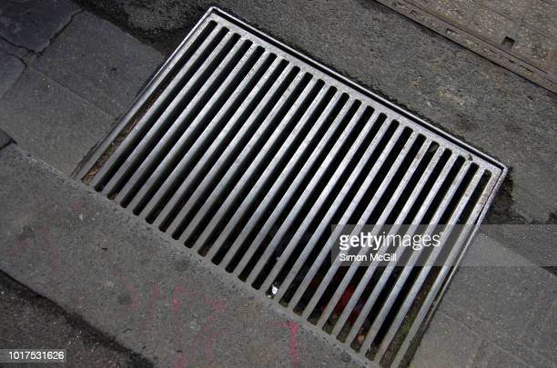 metal sewer drain in a city street - curb stock pictures, royalty-free photos & images