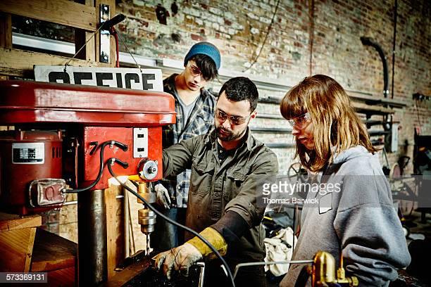 Metal shop owner demonstrating drill press