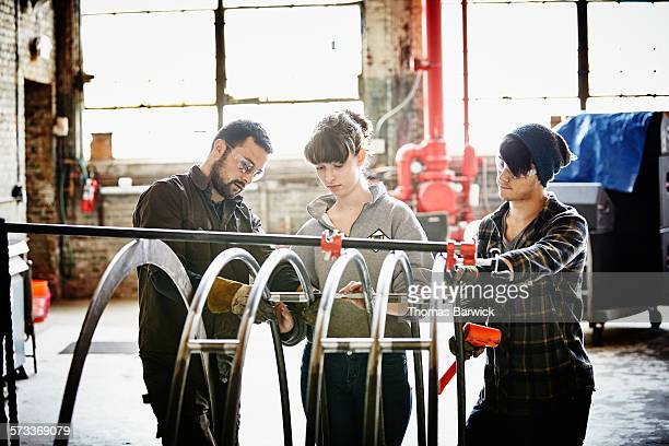 metal shop owner working with two apprentices - leanintogether stock pictures, royalty-free photos & images