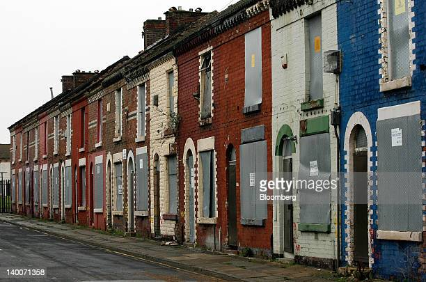 Metal shutters are used to cover windows and doors of houses marked for a housing regeneration project in the Anfield district of Liverpool UK on...