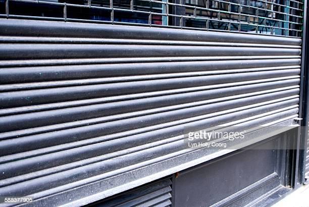 metal shutters on shopfront - lyn holly coorg stock pictures, royalty-free photos & images