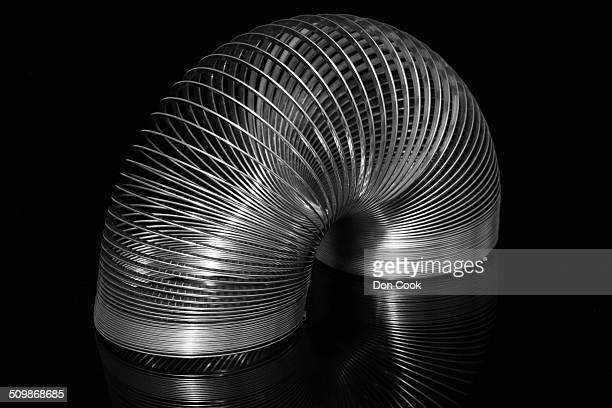metal slinky on black background - metal coil toy stock photos and pictures