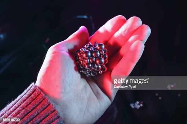 Metal spheres forming a ball shape in hand