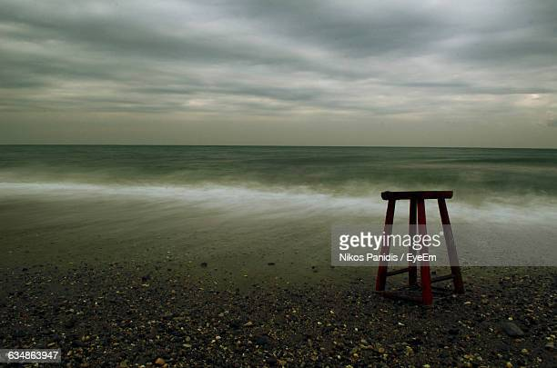 Metal Stool At Beach Against Sky