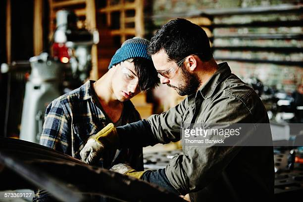 Metal worker and apprentice inspecting project
