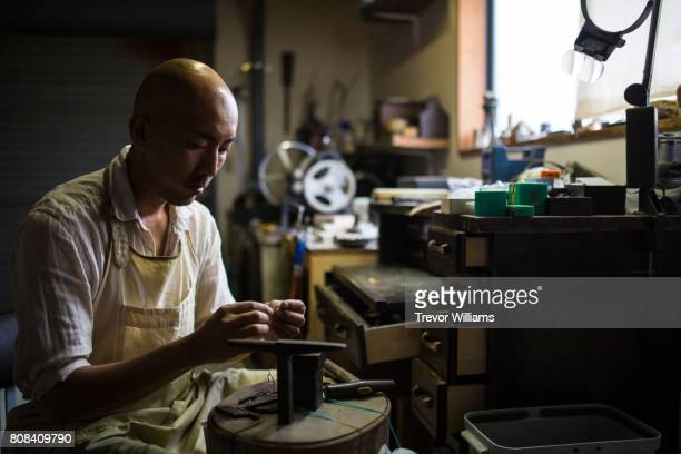 metal worker and jeweller working in his workshop - 美術工芸 ストックフォトと画像
