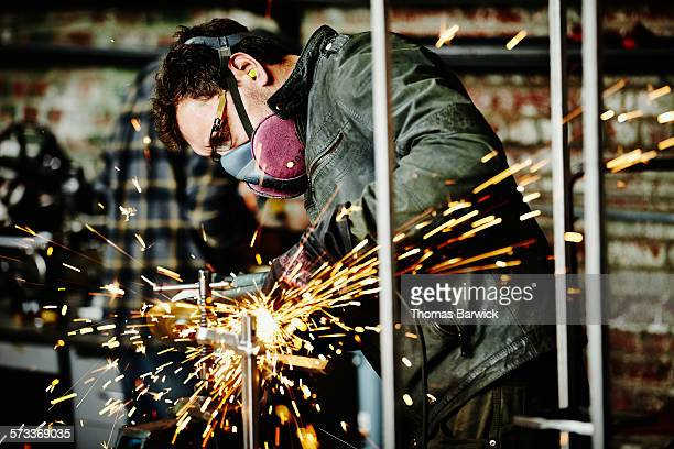 Metal worker cutting steel bar in metal shop
