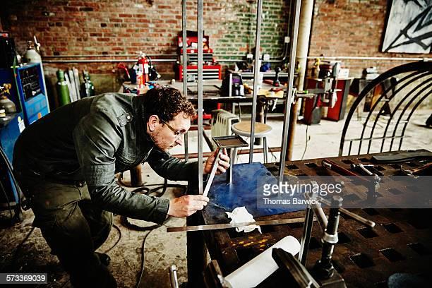 Metal worker inspecting support bar on metal frame