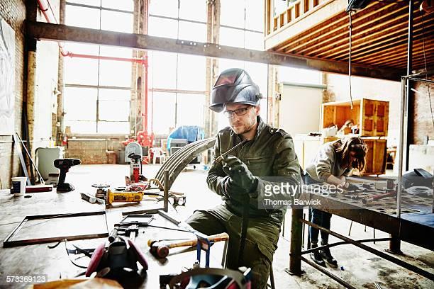 Metal worker preparing to weld metal framing