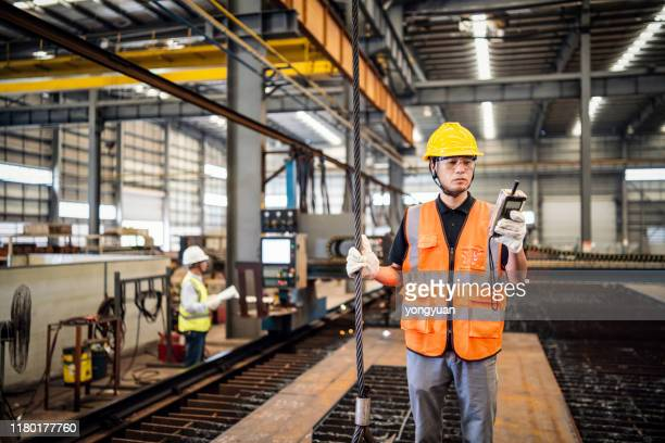 metal worker using a remote controller to operate a crane - crane construction machinery stock pictures, royalty-free photos & images