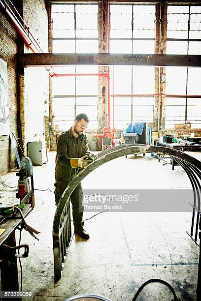 Metal worker using angle grinder to polish project