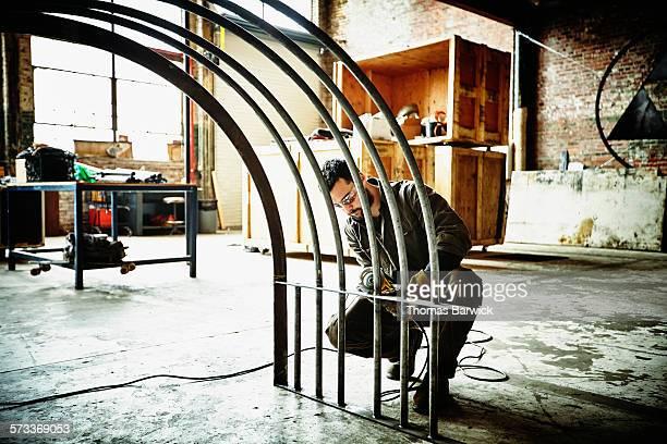 Metal worker using angle grinder to polish railing