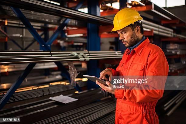 Metal worker using digital tablet in industrial building.
