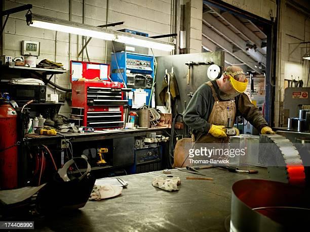 Metal worker using grinder in sheet metal shop
