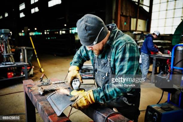 Metal worker using grinder on project in metal shop