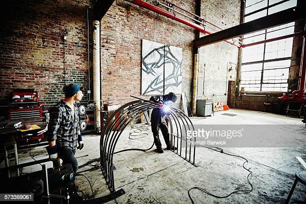 Metal worker welding steel railing in metal shop