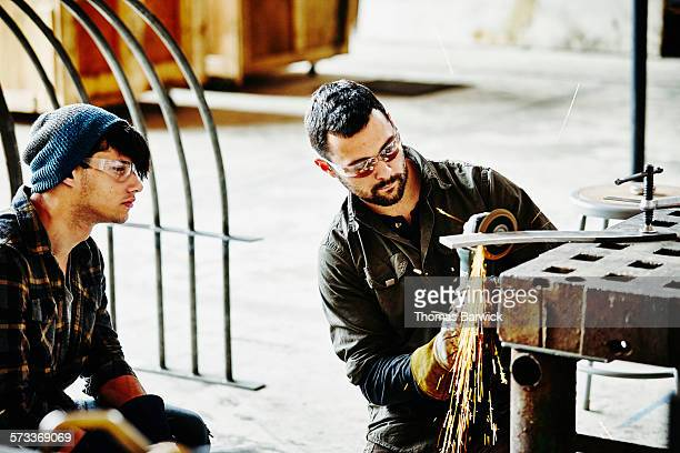 Metal worker working with apprentice in workshop