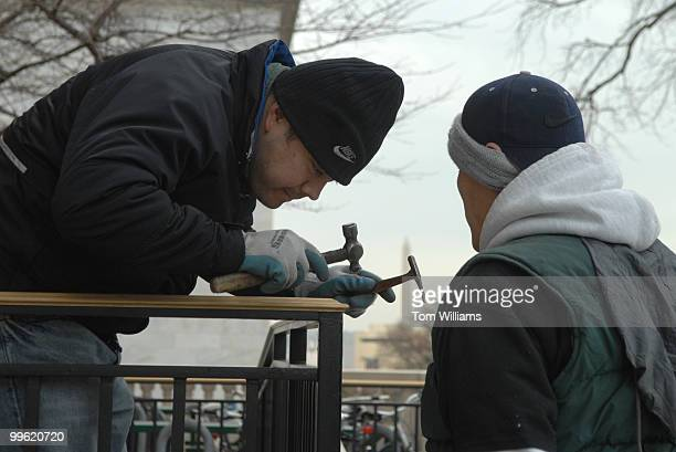 Metal workers Carlos Machuca left and Park Pyung Ok make finishing touches to the brass railing of a new wheelchair ramp outside of Longworth Building