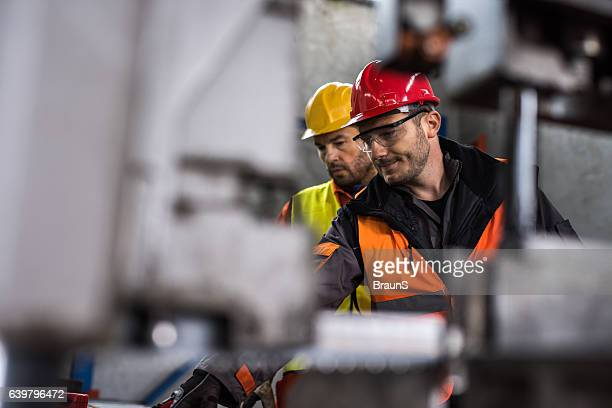 metal workers cooperating while working in aluminum mill. - metallic stock photos and pictures