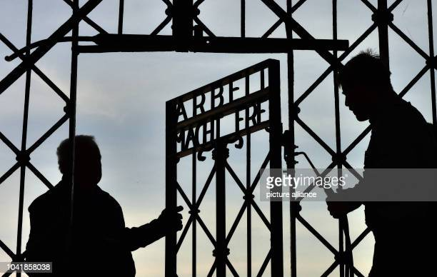 Metal workers install the reconstructed metal gate with the words 'Arbeit macht Frei' in the Dachau concentration camp memorial site in Dachau...