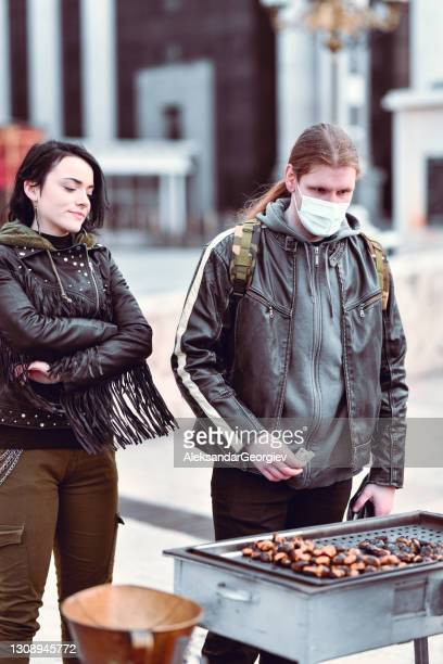 metalhead male with face mask buying girlfriend freshly baked chestnuts outside - punk music stock pictures, royalty-free photos & images