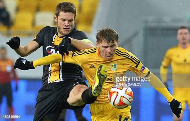 Metalist Kharkiv's Volodymyr Homenyuk vies for the ball with Lokeren's Killian Overmeire during the UEFA Europa League Group L football match between...