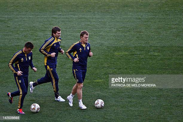 Metalist's defender Serhiy Pshenychnykh and Metalist's Serbian goalkeeper Vladimir DiÅljenkoviÄa and Metalist's defender Andriy Berezovchuk attend to...