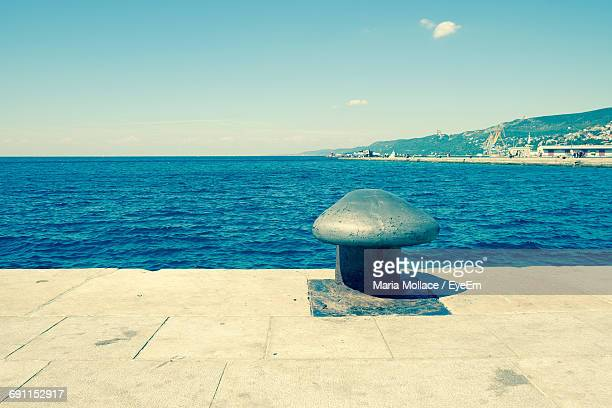 metallic bollard at harbor by sea against sky on sunny day - bollard stock photos and pictures