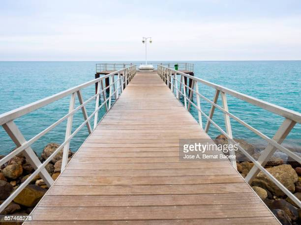 Metallic bridge with wooden floor on the sea surface with a viewpoint. Chilches, Valencian Community,  Castellón /Spain