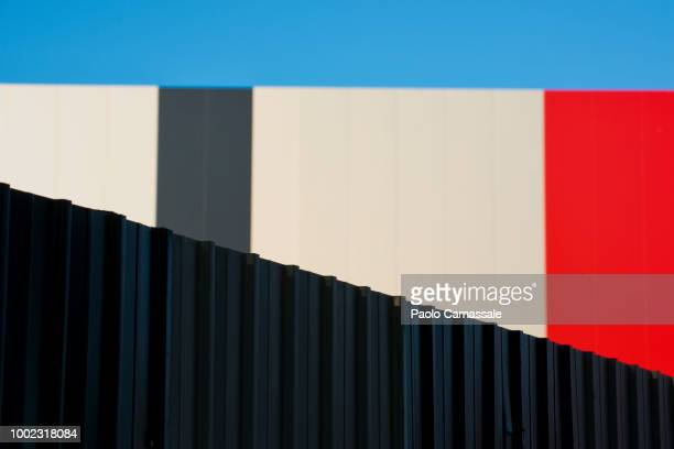 metallic fence against modern colorful wall - wall building feature stock pictures, royalty-free photos & images