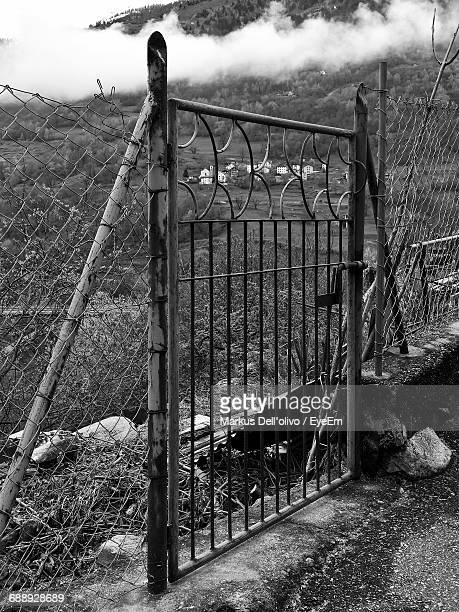 Metallic Gate Amidst Fence By Field