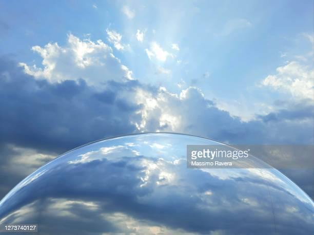 metallic globe reflecting the sky above. - 雰囲気 ストックフォトと画像