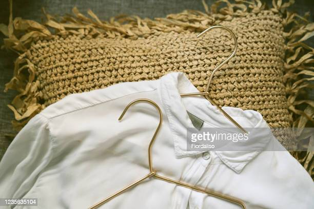 metallic golden hangers and white shirts - metallic dress stock pictures, royalty-free photos & images