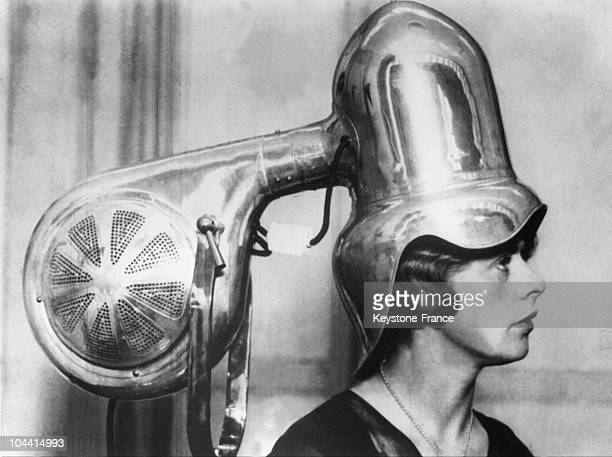 Metallic hairdryer with a young woman underneath in the 1930's