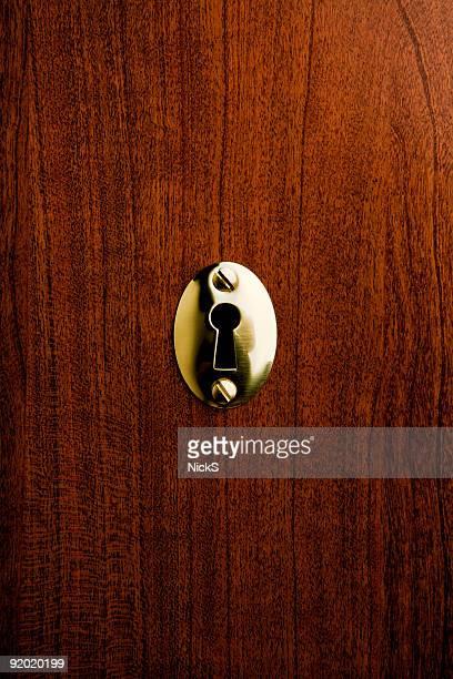 A metallic keyhole on a wooden door