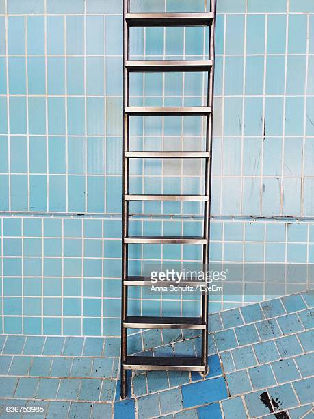 Metallic Ladder Against Blue Tile Wall In Abandoned Swimming Pool