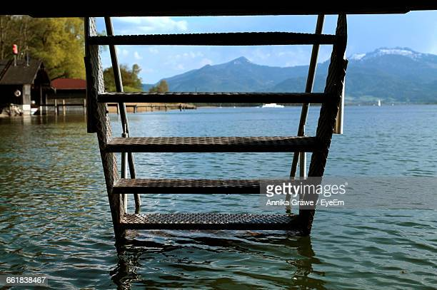 Metallic Ladder In Lake Against Mountain
