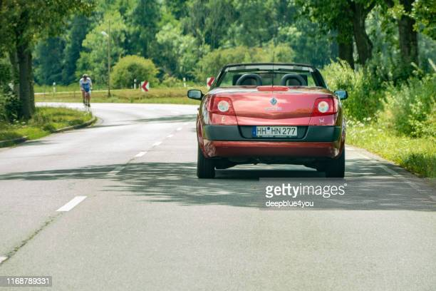 a metallic red renault megane convertible drives in good weather on the main road - renault 4 stock photos and pictures