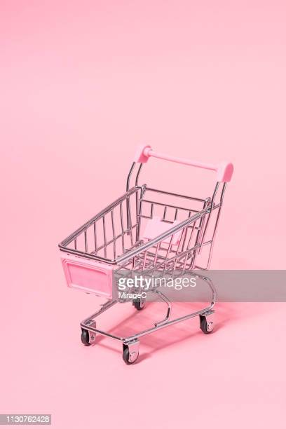 metallic small shopping cart on pink - shopping cart stock pictures, royalty-free photos & images