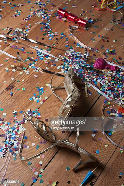 Metallic strappy heels, confetti and streamers littering a hardwood floor