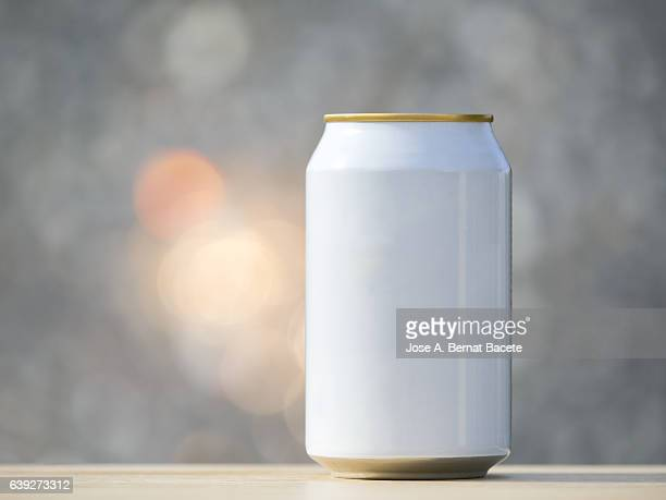 Metallic tin of drinks of refreshment on a table illuminated by the light of the Sun