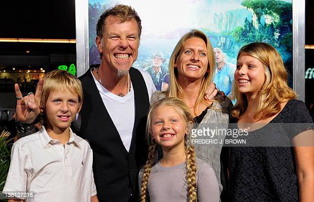 Metallica lead singer James Hetfield gestures while posing with his family on arrival for the film premiere of 'Journey 2 The Mysterious Island' at...