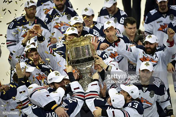 TOPSHOT Metallurg Magnitogorsk team members celebrate as they hold the trophy of the Kontinental Hockey League after winning the final match against...
