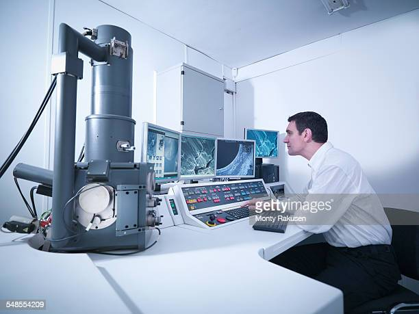 Metallurgist working with electron microscope in automotive test facility