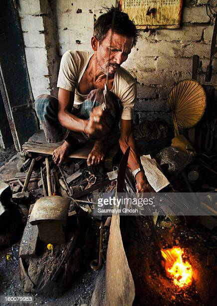 CONTENT] A metalworker is heating an iron bar at his workplace in Kolkata