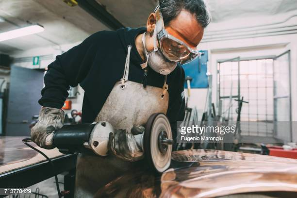 Metalworker polishing copper in forge workshop