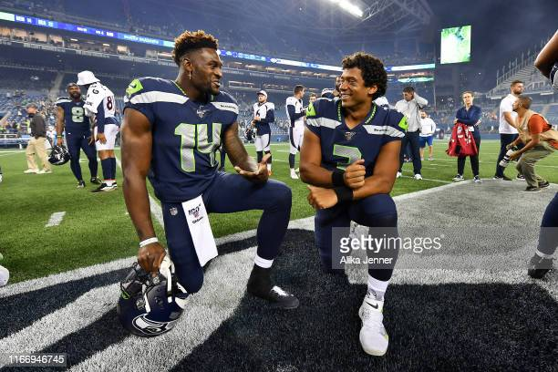 K Metcalf and Russell Wilson of the Seattle Seahawks have a chat after the preseason game victory over the Denver Broncos at CenturyLink Field on...