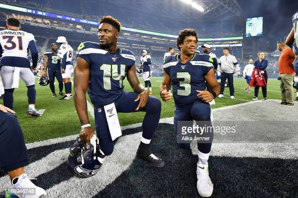 K Metcalf and Russell Wilson of the Seattle Seahawks take a knee after the preseason game victory over the Denver Broncos at CenturyLink Field on...