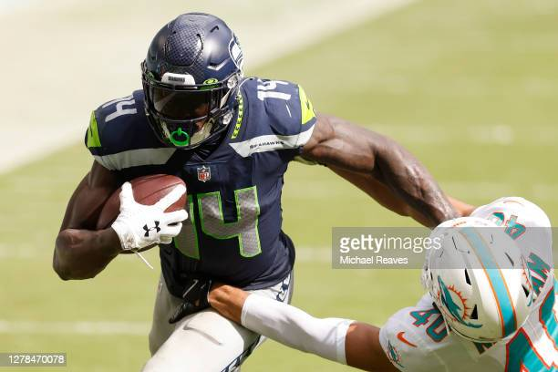 Metcalf of the Seattle Seahawks breaks a tackle from Nik Needham of the Miami Dolphins during the fourth quarter at Hard Rock Stadium on October 04...